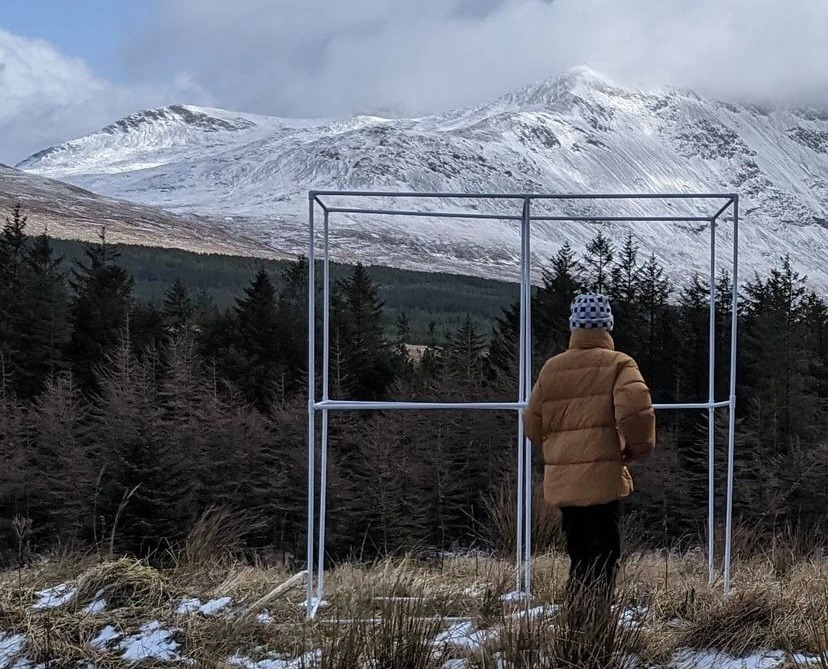 white portable bus stop infront of snowy cuillins with person in orange coat in front