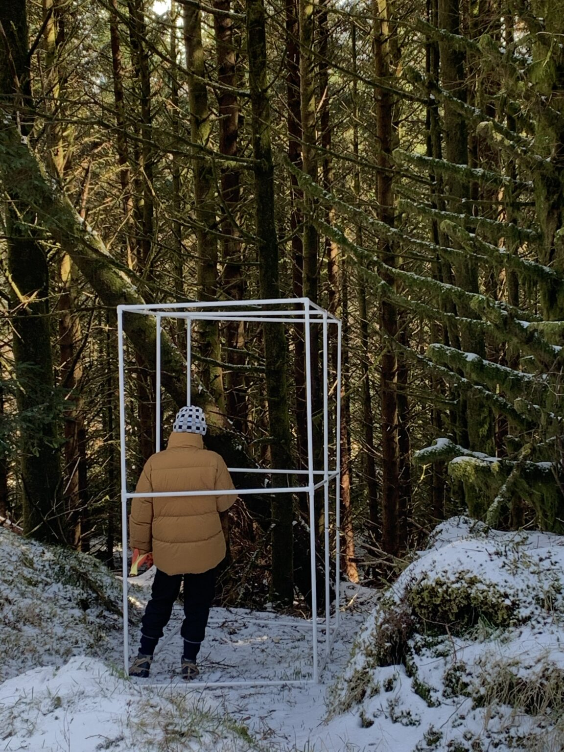 white portable bus stop on snowy ground with dark large forest behind with person inside in a yellow coat