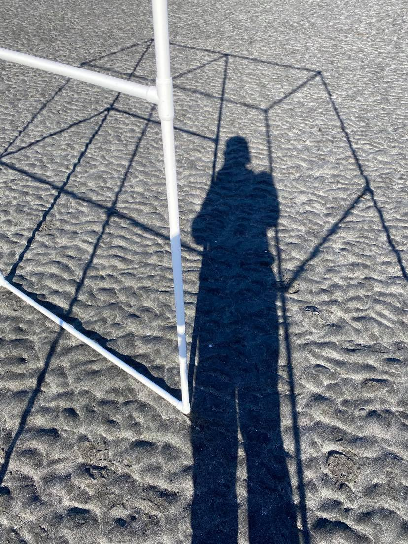 shadow of portable bus stop on the grey sand with person standing in it