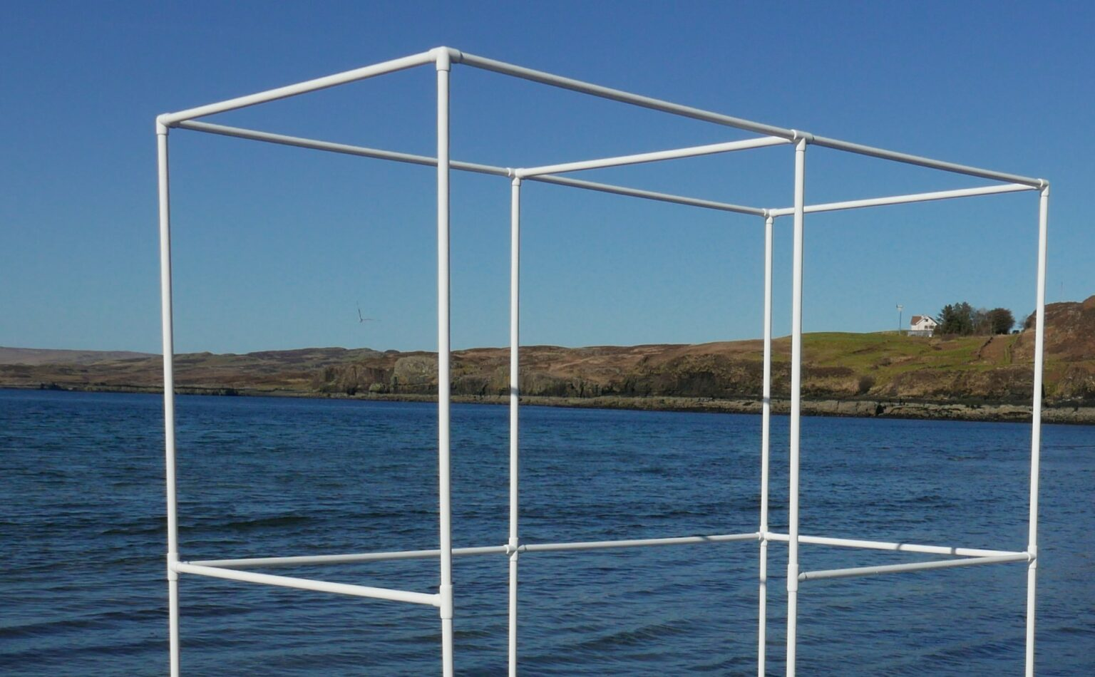 top section of white portable bus stop infront of the sea and blue sky