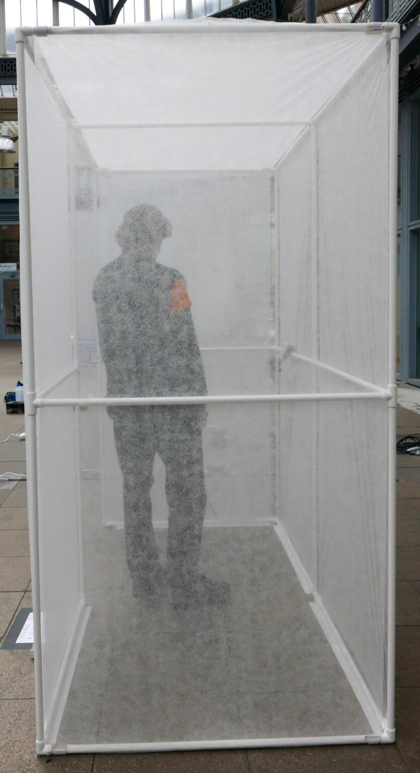 person standing in the portable bus stop at the briggait, their body slightly distorted because of the anti plant freeze
