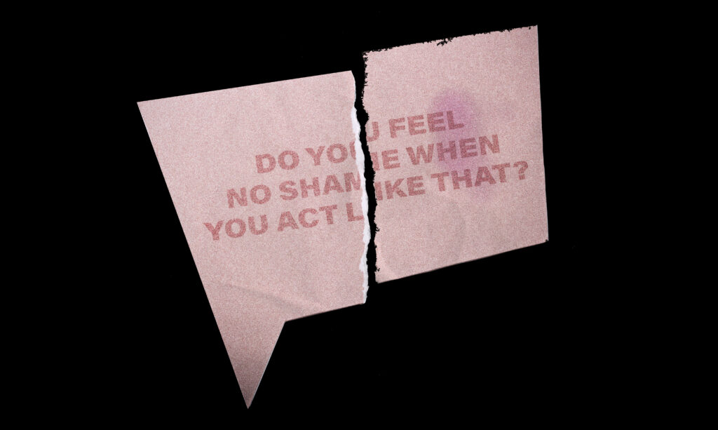 """A half-torn red speech bubble paper on black background with the text """"Do you feel no shame when you act like that?"""""""