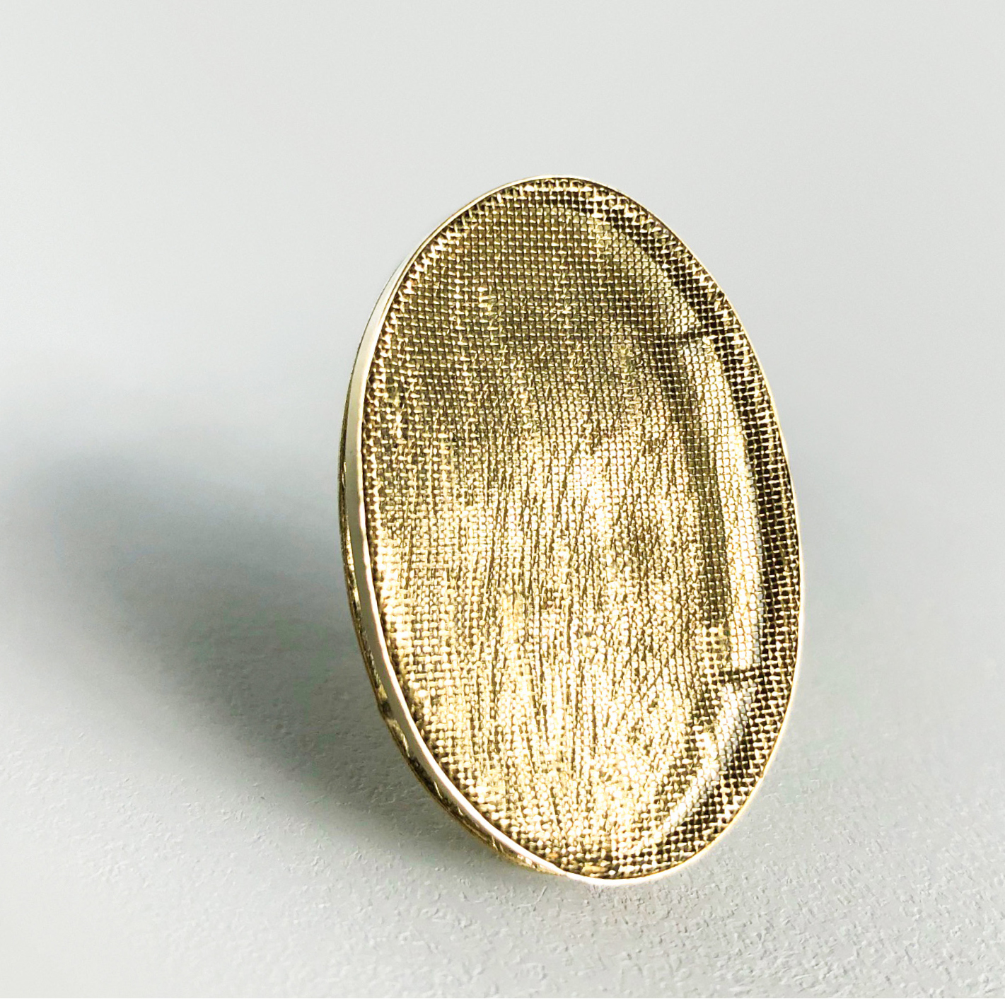 oval brass brooch on white background