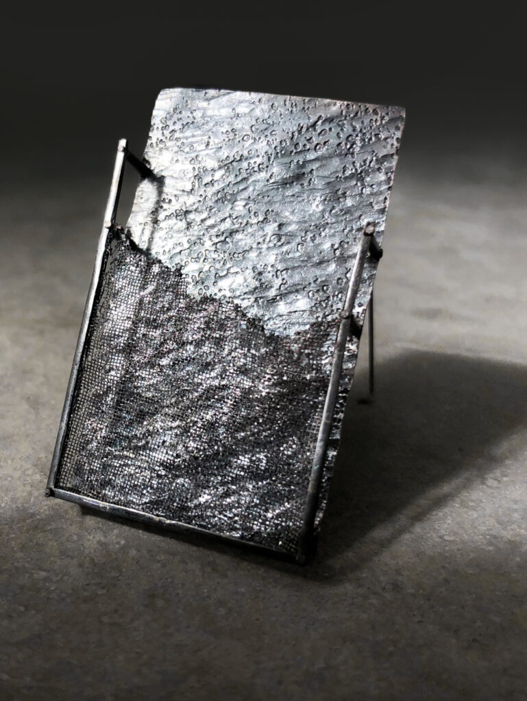 grey rectangle brooch on light grey concrete background