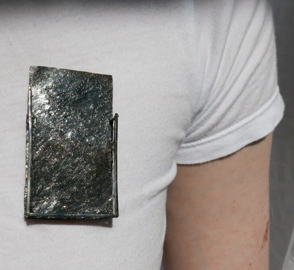 rectangle grey brooch being worn by person wearing a white t-shirt