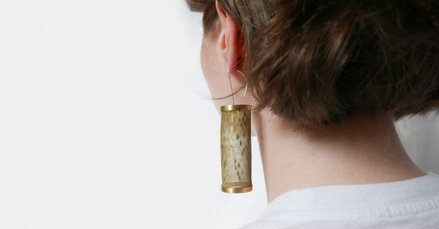 person wearing brass earrings