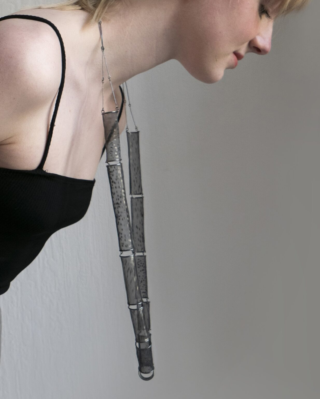 person wearing necklace, leaning so that it hangs away from the body.