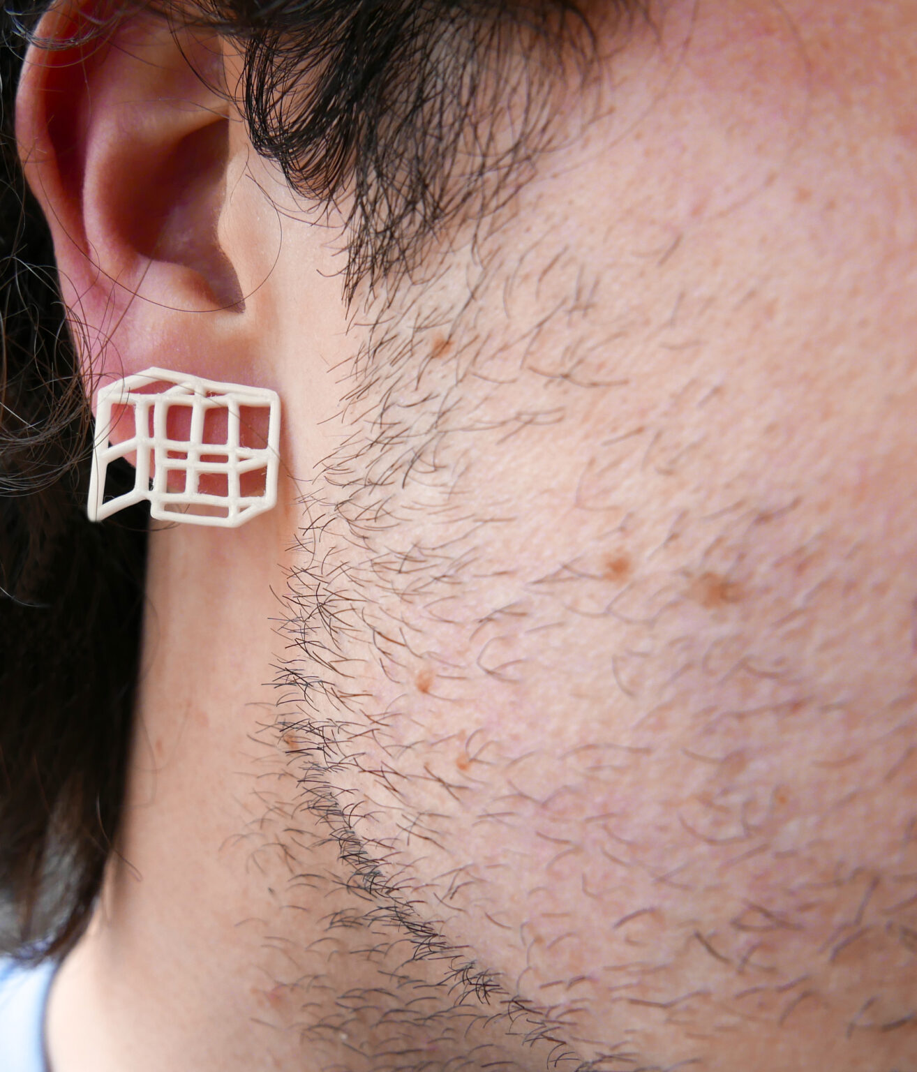 3D printed portable bus stop earring in someone's ear with dark hair and stubble